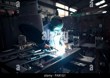 Welder welding metal in a factory - Stock Photo