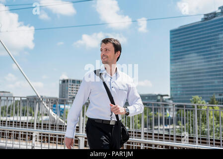Smiling businessman walking on a bridge - Stock Photo