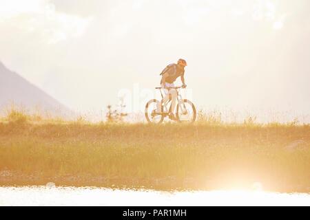 Austria, Tyrol, mountainbiker in the evening light - Stock Photo