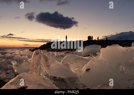 A tourist stands silhouetted against the evening sky as watching the sun set over Diamond Beach in Southern Iceland - Stock Photo