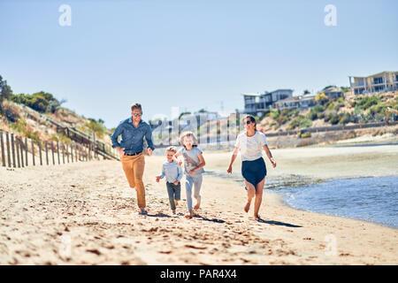 Australia, Adelaide, Onkaparinga River, happy family running on the beach together - Stock Photo