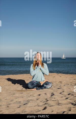 Woman doing yoga on the beach, lotus position - Stock Photo