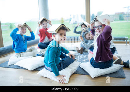 Smiling pupils sitting on the floor in school break room balancing books on their heads - Stock Photo