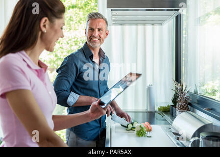 Happy couple in kitchen at home cooking and using a tablet - Stock Photo