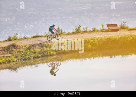 Austria, Tyrol, female mountainbiker at lake in the evening light - Stock Photo