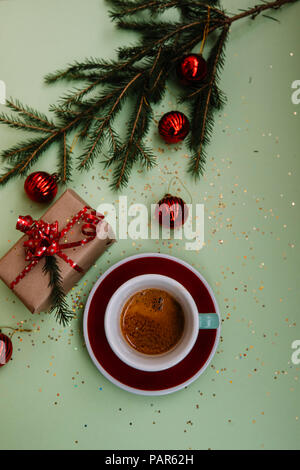 Delicious fresh morning winter festive espresso coffee in a green mug and a red saucer on the green background with christmas decoration - Stock Photo