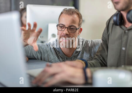 Two colleagues with laptop talking in office - Stock Photo