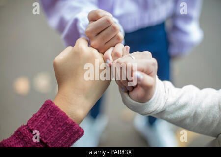 Close-up of teenage girls making a pinky promise - Stock Photo