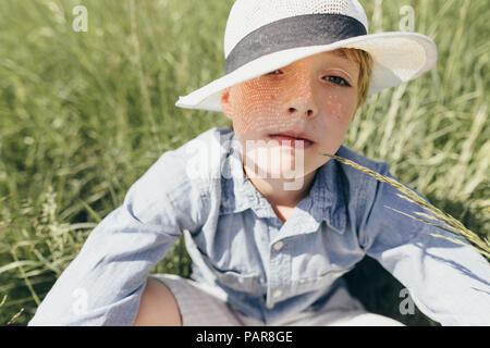 Portrait of boy wearing a hat sitting in field - Stock Photo