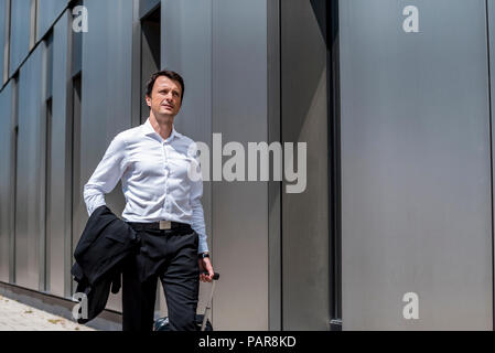 Businessman with rolling suitcase walking in the city - Stock Photo