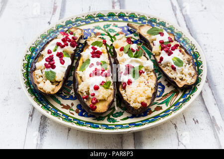 Filled aubergines with couscous, yogurt sauce, mint and pomegranate seeds - Stock Photo
