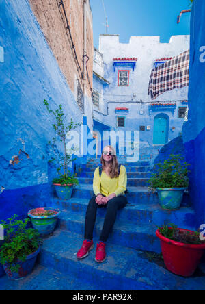 Young woman sits on stairs in the old town, blue house facades, medina of Chefchaouen, Chaouen, Tangier-Tétouan, Morocco