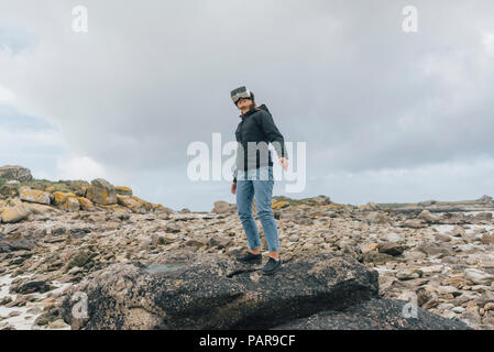 France, Brittany, Landeda, young woman standing at the coast wearing VR glasses - Stock Photo