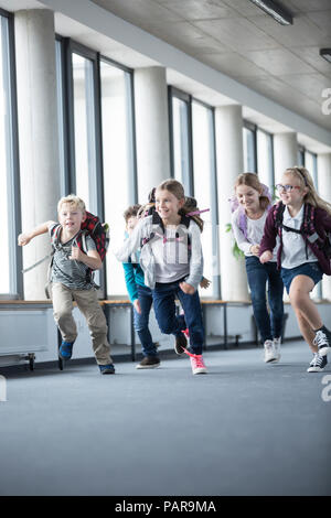Excited pupils rushing down school corridor - Stock Photo