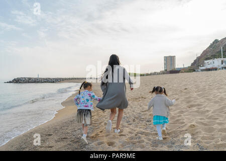 Mother with two daughters running on the beach - Stock Photo