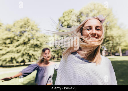 Portrait of two happy young women running in a park - Stock Photo