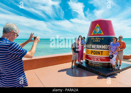 Tourists have their picture taken at the Continental USA's Southernmost Point Sign in Key West, Florida, USA - Stock Photo