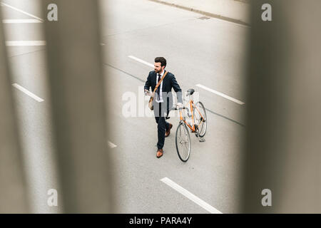 Businessman with bicycle and cell phone walking on the street - Stock Photo