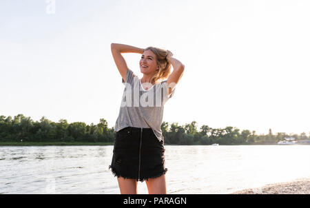 Young woman walking on riverside in the evening - Stock Photo