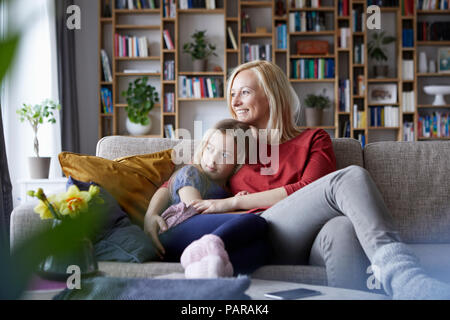 Mother and daughter cuddling on couch - Stock Photo