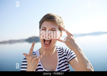 Portrait of screaming woman in front of lake showing Rock And Roll Sign - Stock Photo