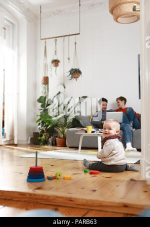 Parents sitting on couch, using laptop, while daughter is playing on the floor - Stock Photo