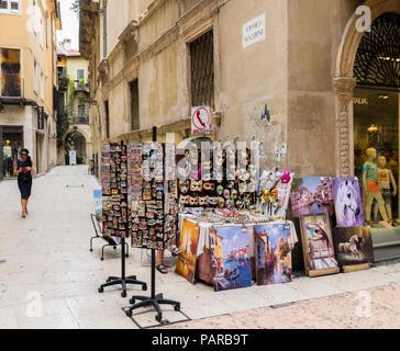 Art stall on a street in Verona italy, market stall, masquerade carnival masks, italiian street stall, vender, oil paintings, artwork on sale - Stock Photo