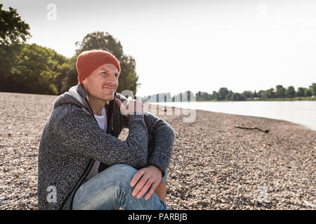 Mature man wearing red beanie sitting at Rhine riverbank - Stock Photo