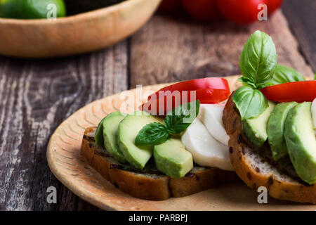 Grilled whole grain bread sandwiches with avocado slices, mozzarella, tomato and basil.  Caprese salad style toasts on rustic ceramic plate - Stock Photo