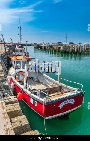 A small fishing boat waits at the quayside to unload its catch in the aqua green waters of West Bay in Dorset. - Stock Photo