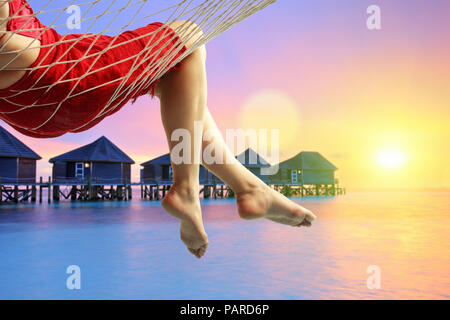 Close-up of a woman lying in a hammock at a water cottages resort - Stock Photo