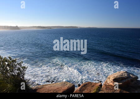 Fog creeping at Northern beaches on a sunny afternoon in winter time. View from Cabbage Tree Reserve lookout. - Stock Photo