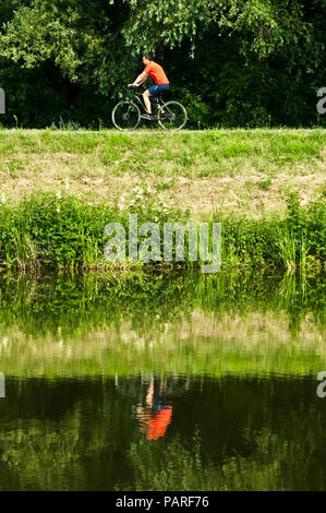 man riding a bicycle in nature along a river and reflection of him in the water - Stock Photo