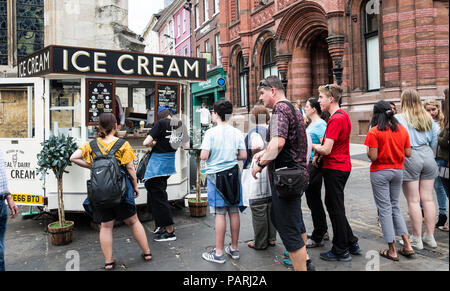 A long queue of people waiting in line at an old fashioned ice cream stand during a heatwave and hot weather in York, UK - Stock Photo