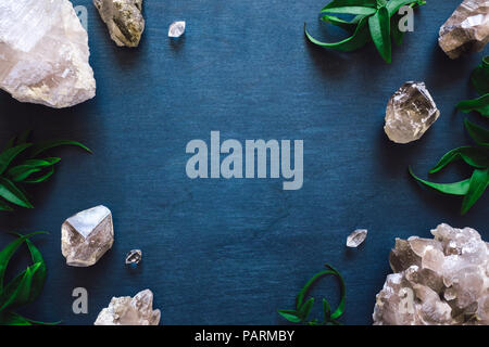 Frame with Clear and Smoky Quartz and Botanicals on Blue Table - Stock Photo