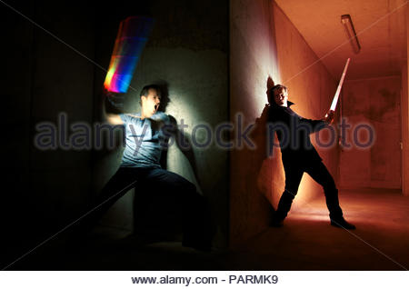 Two men standing in an illuminated corridor of a building indoors - Stock Photo