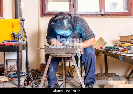 Sculptor is using arc welding to assembly metal sculpture barehanded with protective mask. - Stock Photo