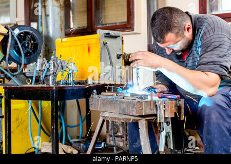Sculptor is using arc welding to assembly metal sculpture without proper protection, barehanded. - Stock Photo