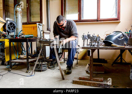 Sculptor is using arc welding to assembly metal sculpture barehanded with protective spectacles. - Stock Photo