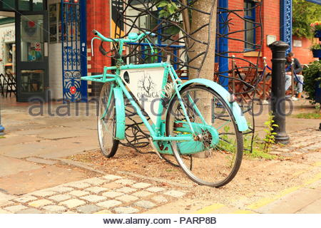 A quirky bicycle advertising the Oak Street Cafe at The Manchester Craft & Design Centre on Old Street. Northern Quarter, Manchester UK - Stock Photo