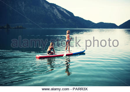 Two girls enjoying a canoe ride together in the lake - Stock Photo