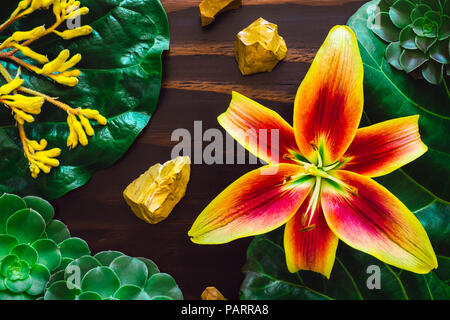 Yellow Lily with Yellow Jasper and Mixed Botanicals on Wood Table - Stock Photo