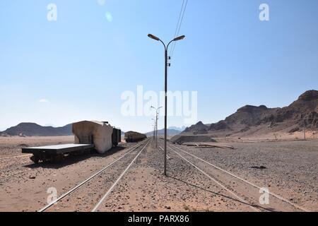 Train tracks and deserrted transport train in wadi rum desert area - Stock Photo