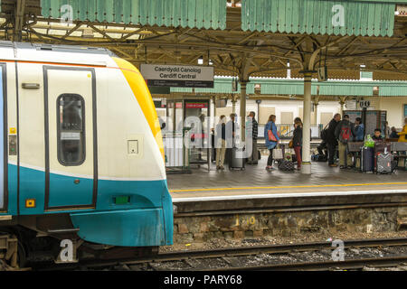 Passengers on platform at Cardiff Central Station with the front of a diesel train in view. - Stock Photo