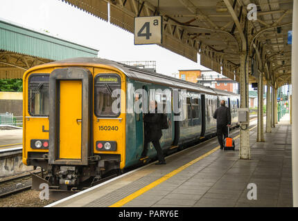 Diesel commuter train alongside a platform in Cardiff Central Station. A driver is entering the cab and a person is pulling a suitcase along the platform - Stock Photo