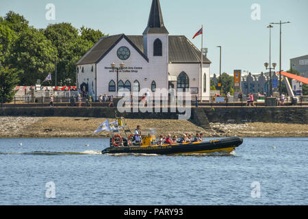 High speed inflatable boat taking visitors out for a trip around Cardiff Bay. In the background is the landmark Norwegian Church - Stock Photo