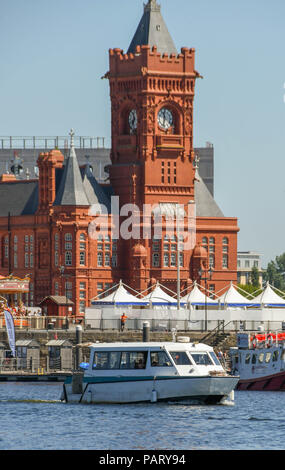 Small water taxi taking passengers across Cardiff Bay passing the landmark Pierhead Building - Stock Photo