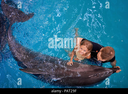 child swims with a Dolphin - Stock Photo