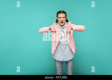 here and now. serious bossy portrait of beautiful cute girl standing with makeup and brown pigtail hairstyle in striped blue shirt pink jacket. indoor - Stock Photo