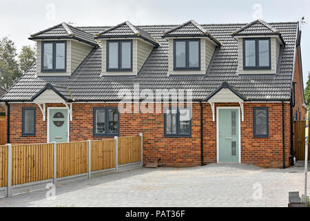 Front of new semi detached housing home just completed house building paved over front garden car parking in existing suburban street Brentwood UK - Stock Photo
